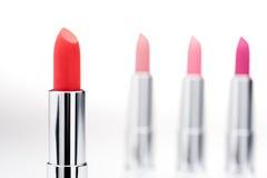Rossetto rosso affascinante con l'insieme dei rossetti rosa dietro Fotografia Stock