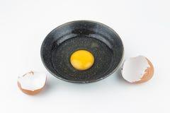 Rossi d'uovo uno in ciotola nera e nelle coperture rotte dell'uovo Fotografie Stock