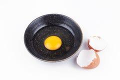 Rossi d'uovo uno in ciotola nera e nelle coperture rotte dell'uovo Fotografia Stock