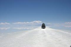 Rossing de zoute vlakten van salar DE uyuni in Bolivië door suv Royalty-vrije Stock Foto's