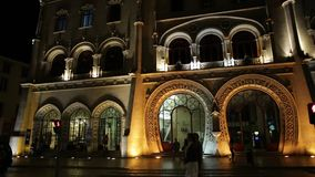 Rossio Station by night. Lisbon, Portugal - August 24, 2017: people at entrance of Rossio Railway Station illuminated at night in Rossio Square, Lisbon downtown stock video footage