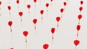 Rosso che gioca i dardi anche in una griglia su una superficie di calcestruzzo semplice Fotografia Stock