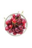 Rosso ciliegia con i cali in una ciotola di vetro su un fondo bianco Immagine Stock