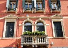 Rosso del palazzo con il balcone fiorito in Veneto (Italia) Immagini Stock