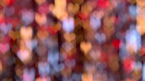 Rosso delicato, giallo, blu accende il fondo dell'estratto del bokeh a forma di cuore video d archivio