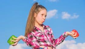 Rosso della tenuta della ragazza del bambino e fondo del cielo dei peperoni verdi Bambino che presenta i generi di pepe Caduta ma fotografia stock libera da diritti