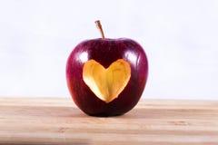 Rosso di Apple con cuore sul tagliere di legno Immagine Stock Libera da Diritti