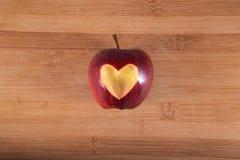 Rosso di Apple con cuore sul tagliere di legno Fotografia Stock Libera da Diritti