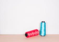 Rosso e filati cucirini blu su chiaro fondo Fotografia Stock Libera da Diritti