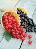 Rosso e ribes nero nei coni della cialda su fondo di legno rustico Dessert dietetico e sano Immagini Stock