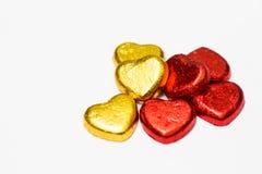 Rosso ed isolato della caramella di cioccolato del cuore dell'oro su fondo bianco Immagine Stock