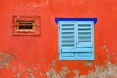 Rosso, sbucciando facciata e una finestra di legno blu Fotografia Stock