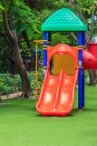 Rosso si raddoppiano gli scorrevoli per i bambini su prato inglese verde Immagini Stock