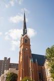 Rost färgad kyrklig kyrktorn på den trevliga skyen royaltyfri foto