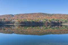 Rost färgat nedgånglandskap på den lugna sjön Arkivfoto