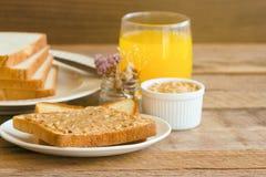 Rosta bröd med hemlagat jordnötsmör som tjänas som med orange fruktsaft Royaltyfri Bild