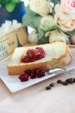 Rosta bröd och sött rött jordgubbedriftstopp som är klara att äta på plattan Royaltyfria Bilder