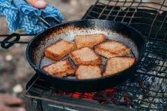 Rosta bröd som grillar på brand som campar i naturen Arkivbilder