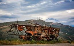 Rosta och förfalla skördetröskan som överges på bergvägrenen med dramatiska berg bakom royaltyfri foto