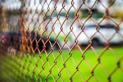 Rosta stål som är netto med suddighetsfotbollfältet arkivbilder