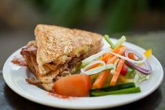 Rostad bacon- och äggsmörgås med sallad Arkivbild
