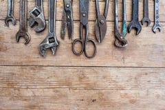 Rostade övre siktstappning för slutet hjälpmedel på den gamla trätabellen: plattång, rörskiftnyckel, skruvmejsel, hammare, metall Royaltyfria Bilder