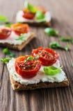 Rostade bröd (Crostini) med ricotta och körsbärsröda tomater Arkivfoton