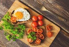 Rostade bröd med ägget och stekte tomater Royaltyfria Bilder