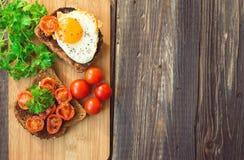 Rostade bröd med ägget och stekte tomater Arkivbilder