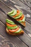 Rostade bröd med avokadot och tomaten på en trätabell Royaltyfri Bild