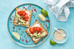 Rostade bröd med fetaost, tomater, avokadot, granatäpplet, pumpafrö och flaxseedgroddar Banta den sund frukosten som är läcker oc royaltyfri fotografi