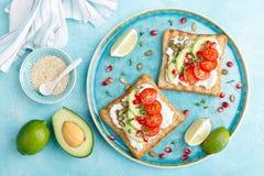 Rostade bröd med fetaost, tomater, avokadot, granatäpplet, pumpafrö och flaxseedgroddar Banta den sund frukosten som är läcker oc royaltyfri foto