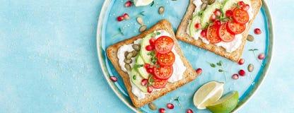 Rostade bröd med fetaost, tomater, avokadot, granatäpplet, pumpafrö och flaxseedgroddar Banta den sund frukosten som är läcker oc royaltyfri bild