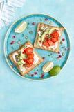 Rostade bröd med fetaost, tomater, avokadot, granatäpplet, pumpafrö och flaxseedgroddar Banta den sund frukosten som är läcker oc arkivbild