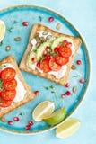 Rostade bröd med fetaost, tomater, avokadot, granatäpplet, pumpafrö och flaxseedgroddar Banta den sund frukosten som är läcker oc arkivbilder
