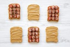 Rostade bröd med jordnötsmör, jordgubbar och chiafrö på en vit träbakgrund, bästa sikt fotografering för bildbyråer