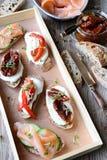 Rostade bröd med laxen, torkade tomater och söta peppar Royaltyfria Bilder