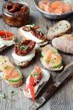 Rostade bröd med laxen, torkade tomater och söta peppar Arkivbild