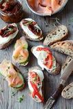 Rostade bröd med laxen, torkade tomater och söta peppar Arkivbilder