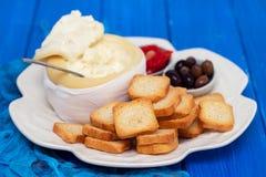 Rostade bröd med ost, oliv och röd peppar på den vita maträtten royaltyfria bilder