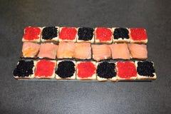 Rostade bröd med röda och svarta ägg av klumpa sig och laxen Royaltyfri Fotografi