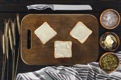 Rostade bröd med smör och spikelets Arkivfoto