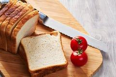 Rostade bröd på brädet, kniven och tomaterna royaltyfri foto
