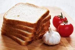 Rostade bröd på brädet och grönsakerna royaltyfria bilder