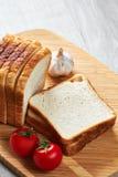Rostade bröd på brädet och grönsakerna royaltyfria foton