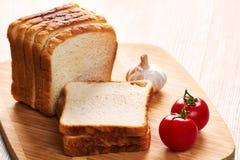 Rostade bröd på brädet och grönsakerna arkivfoton