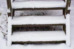 Rostade moment av en metallstege som täckas med snö Arkivbilder