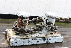 Rostade skeppsdockadubbar med att förtöja kedjar fast fäst - grunge - målarfärg för flagnande vit - på marina arkivbilder