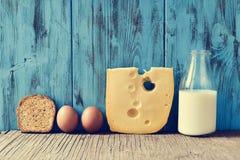 Rostat bröd ägg, ost och mjölkar på en lantlig trätabell, med en fi royaltyfria bilder