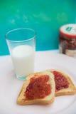 Rostat bröd för jordgubbedriftstopp och ett exponeringsglas av mjölkar Fotografering för Bildbyråer